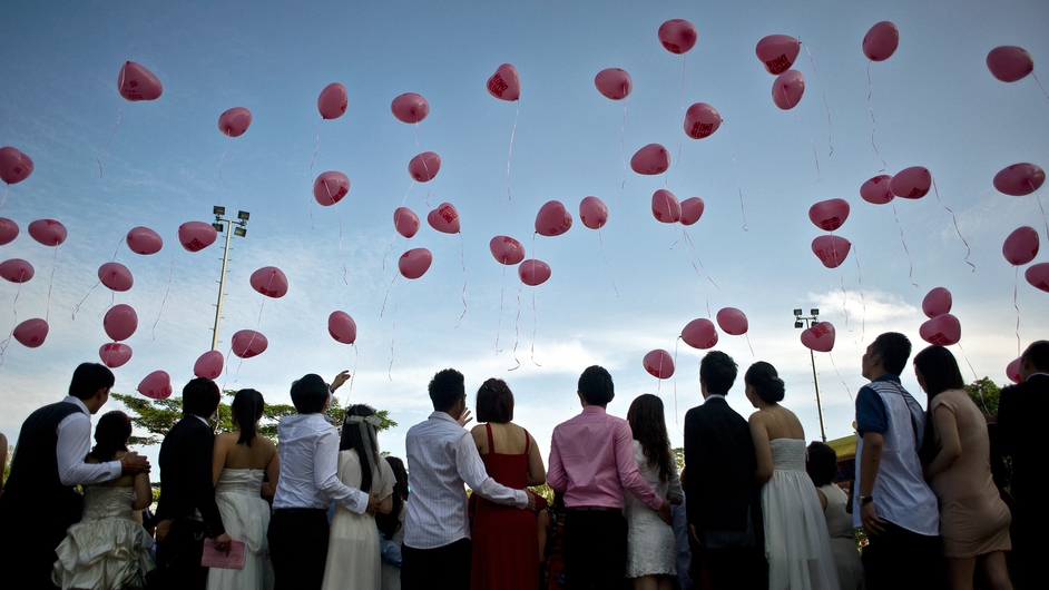 Newly-wed ethnic Malaysian-Chinese couples release heart-shaped balloons during their mass wedding ceremony on Valentine's Day at the Thean Hou Temple in Kuala Lumpur