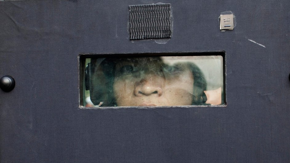 A Thai police officer peers through the eye slit of his riot shield as police storm an anti-government protest camp near Government House in Bangkok