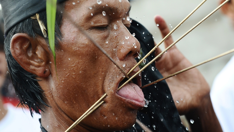 A Tatung pierces metal needles trough his cheeks during the Tatung Festival as part of Cap Go Meh celebrations in Singkawang, Kalimantan, Indonesia. The ancient art of Tatung is believed to call upon positive spirit who help to dispel the bad spirits that