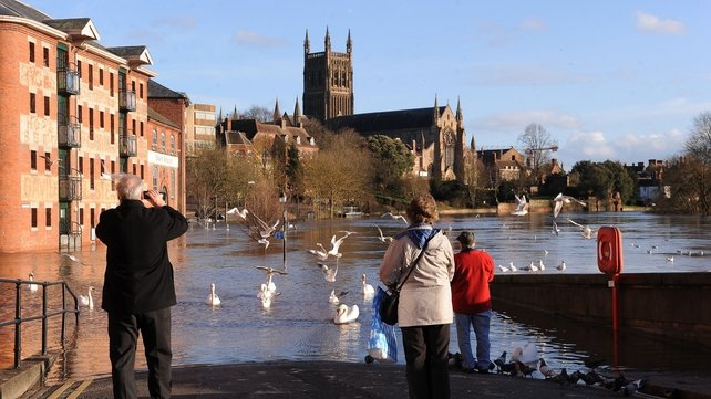 People take pictures of the River Severn, in flood-hit Worcester, which has reached its highest level in recent years