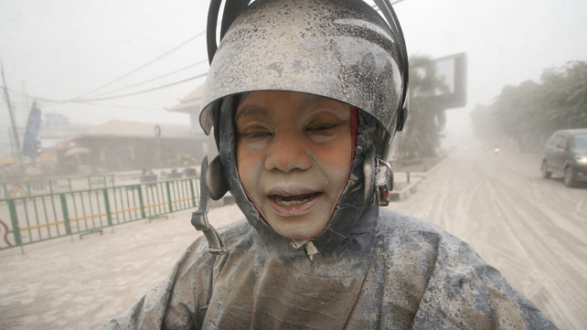 An Indonesian woman covered with ash from the Mount Kelud volcano is seen at a roadside in Yogyakarta (Pic: EPA)