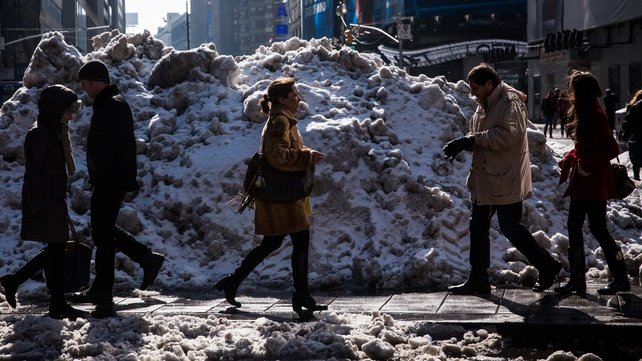 People walk past a pile of snow in Times Square in New York City