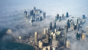 An aerial view of high-rise buildings emerging through fog covering the skyline of Doha (Pic: EPA)