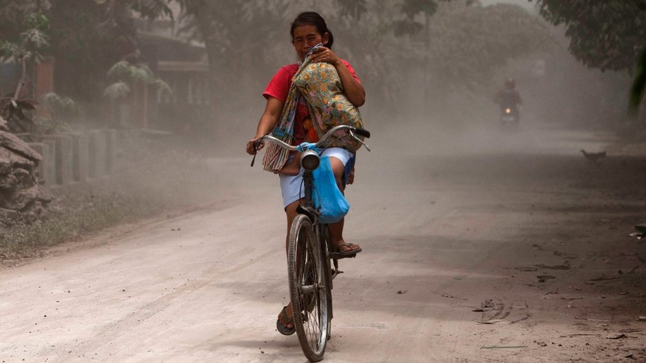 Woman cycles to safety with her child as ash spews from Mount Kelud