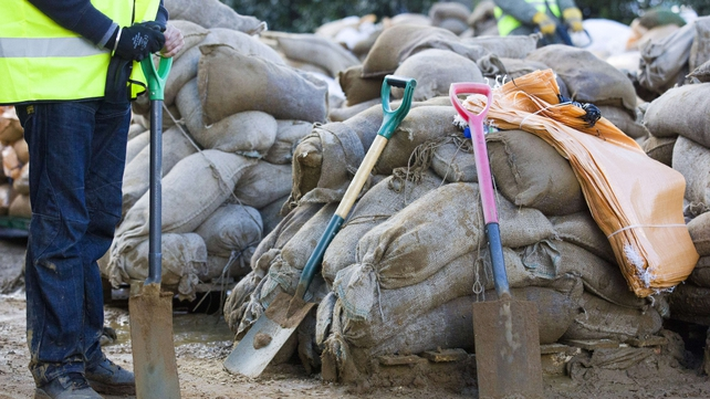A volunteer stands by with a spade as he joins others in filling sandbags to be distributed to combat flooding in Egham, west of London,