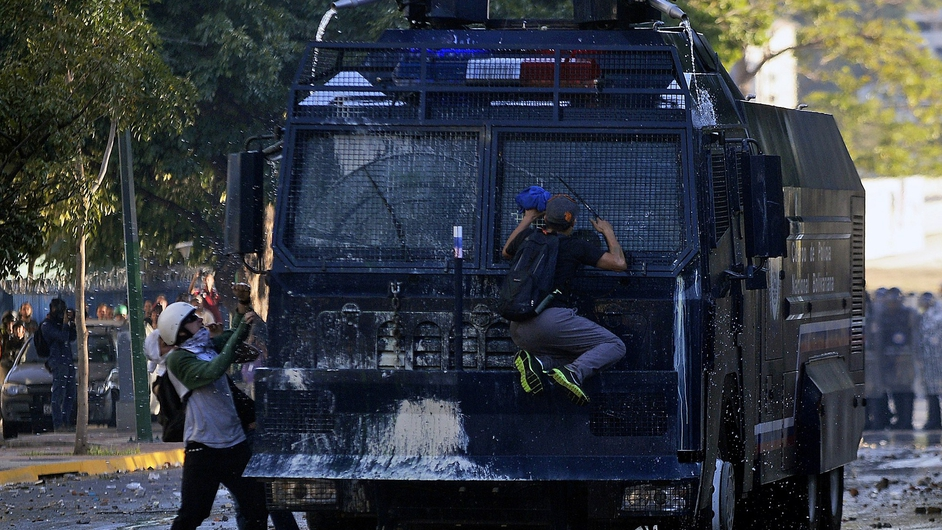 Anti-government students attack a water cannon during a protest in Caracas. Supporters and opponents of Venezuela's leftist government staged rallies in the capital.