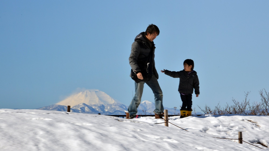 A boy and his father walk on a snow covered field in Tokyo while snow covered Mount Fuji is seen in the background. Two people were killed when a fresh snow storm hit Japan, disrupting rail and road travel, and grounding more than 100 flights.