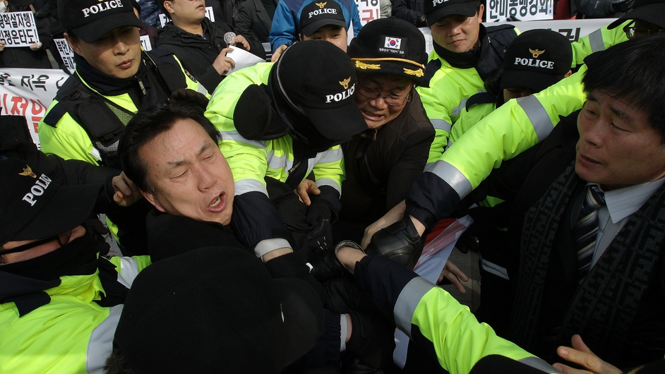 South Korean conservative protesters scuffle with riot police as police seize a North Korean flag from the demonstrators during an anti-North Korea protest in Seoul. The rally coincided with North Korean leader Kim Jong Il's birthday.