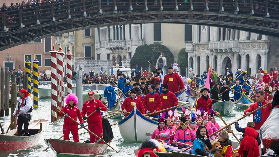 Rowers dressed in costumes take part in the traditional regatta on the Grand Canal which officially opens the Venice Carnival