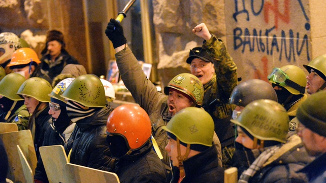 Activists of 'Maidan self-defence' react as they guard Kiev's city hall in order to prevent its capture
