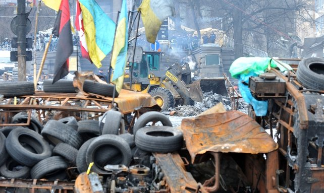 A backhoe loader tractor of the Kiev communal services removes an opposition barricade on Grushevsky street