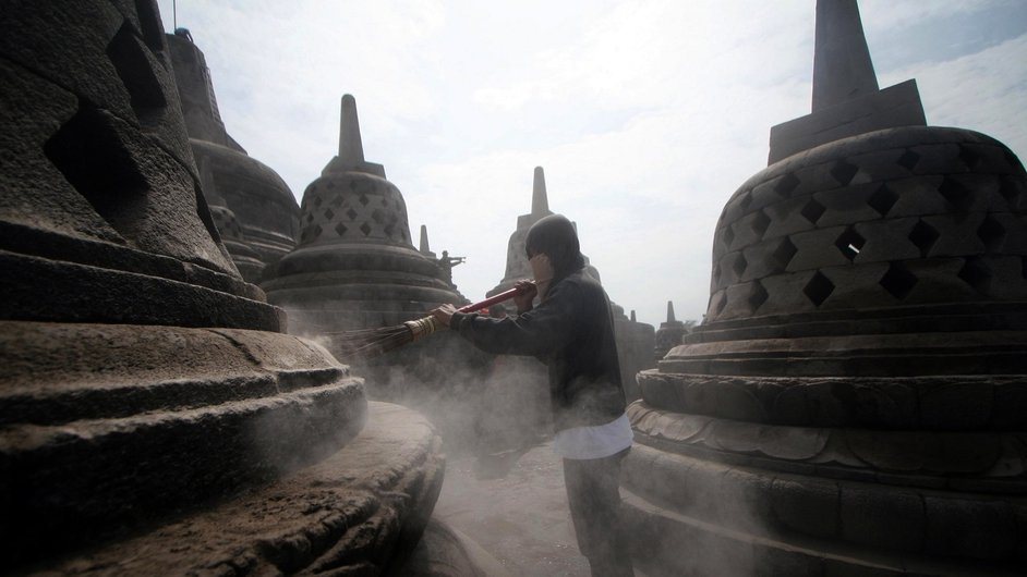 An Indonesian volunteer removes volcanic ash from a Buddha stupa at Borobudur temple in Magelang, Central Java, Indonesia (Pic: EPA)