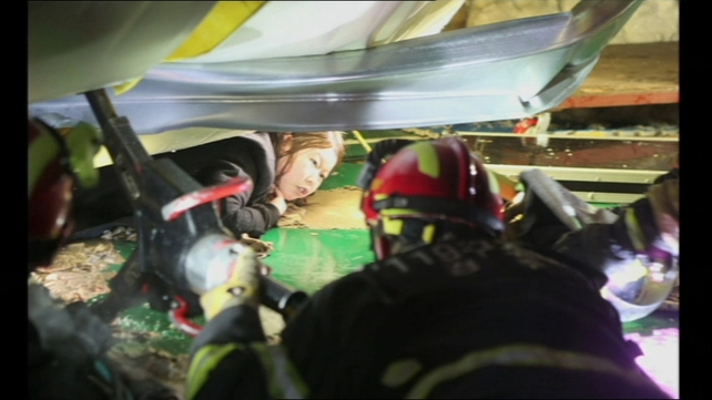 Rescue workers try to free a woman trapped underneath the wreckage of the building
