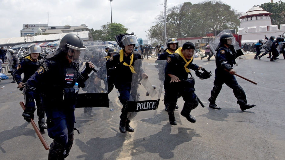 Police officers run amid the sound of explosions in Bangkok