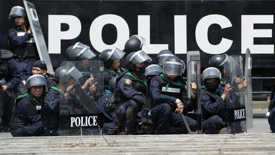 Thai riot policemen stand guard after demanding protesters to leave the area