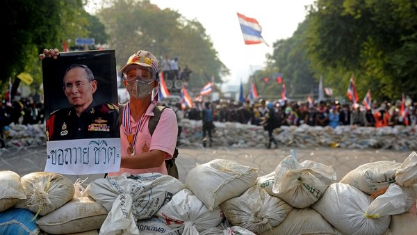 An anti-government protester holds a poster of Thai King Bhumibol Adulyadej during the stand-off near Government House in Bangkok