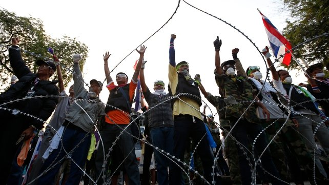 Protesters shout slogans from behind barbed wire at a protest site near Government House in Bangkok (Pic: EPA)