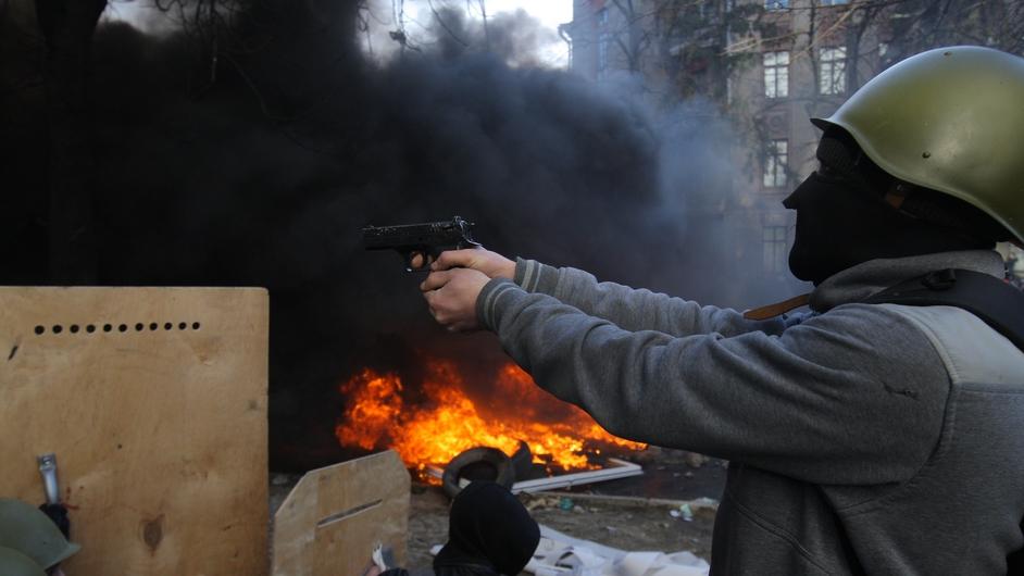 A protester aims a gun at police (Pic: EPA)