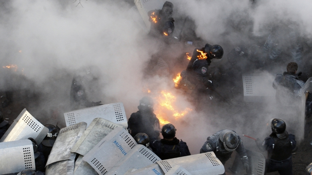 Policemen run amid flames during clashes in front of the Ukrainian Parliament
