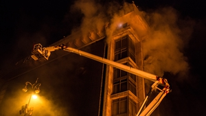 A fire truck is used to rescue people from the upper floors of the burning Trade Unions Building