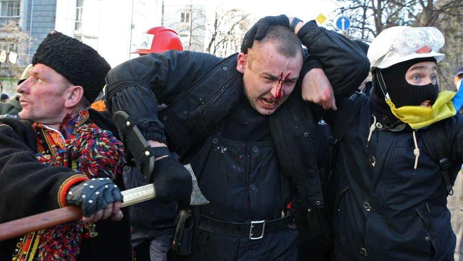 An injured  policeman is escorted during the protests (EPA)