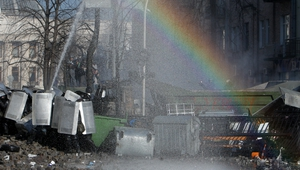 Protesters clash with riot police as a rainbow appears during continuing protests in downtown Kiev (EPA)