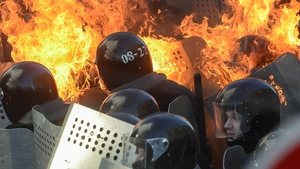 Police threw stun grenades at protesters separated from them by a line of burning tents, tyres and wood