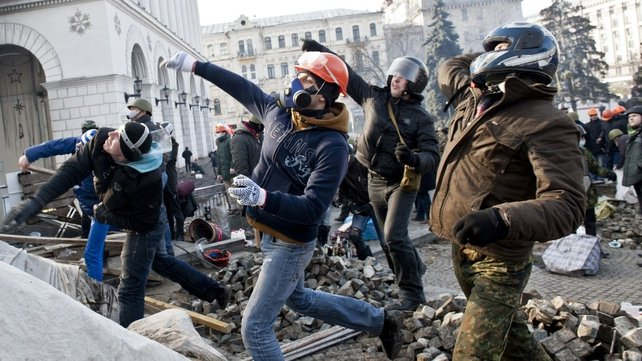 Protesters throw rocks at riot police during sporadic clashes today