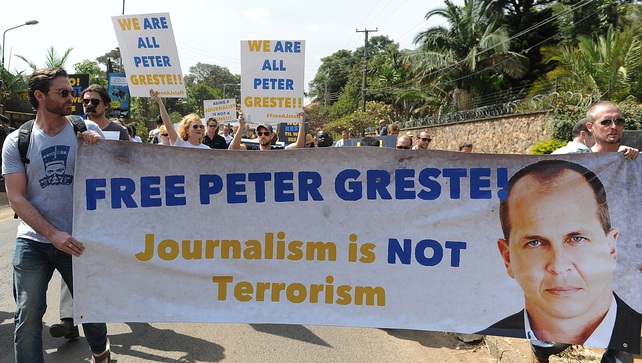Foreign journalists hold banners bearing a picture of Peter Greste during a protest against his detention