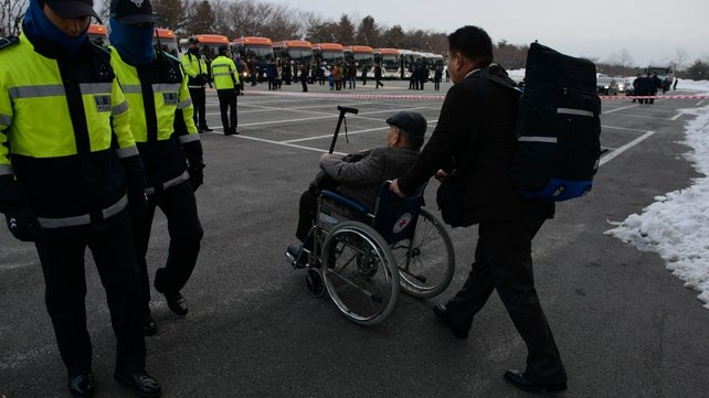 A man in a wheelchair is pushed towards a waiting bus preparing to depart for joint North and South Korean family reunions