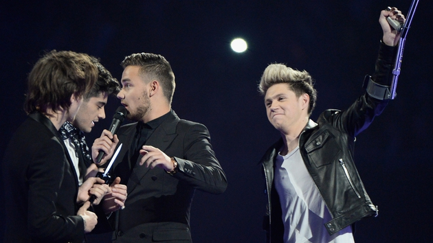 Niall Horan raises a crutch to the crowd at last night's Brit Awards while on stage with his One Direction band members