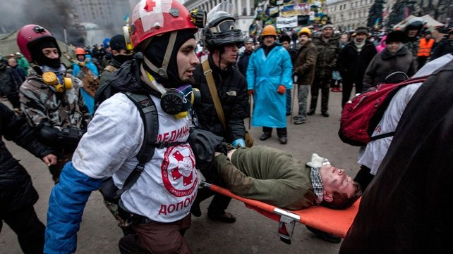 Medics carry a wounded man from Independence Square (Pic: EPA)