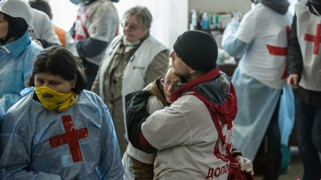 A woman is comforted in the Hotel Ukraine which has been turned into a makeshift medical centre