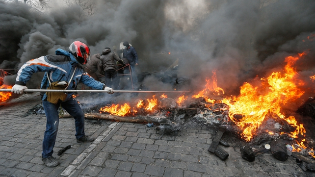 A protester burns tyres forming a barricade in Independence Square