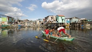 Filipino children riding on a makeshift boat manoeuvre along a shanty town in Navotas city, north of the capital Manila (Pic: EPA)
