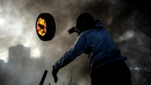 An anti-government demonstrator throws a burning tyre as he builds a barricade in the centre of Kiev