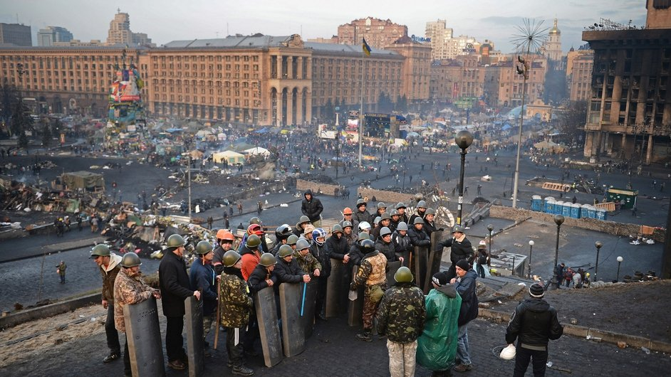 Anti-government protesters man the front line barricades following clashes with police in Independence Square in Kiev
