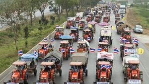 A convoy of tractor-riding farmers return to their home after a demonstration on the highway in Ayutthaya province in Thailand