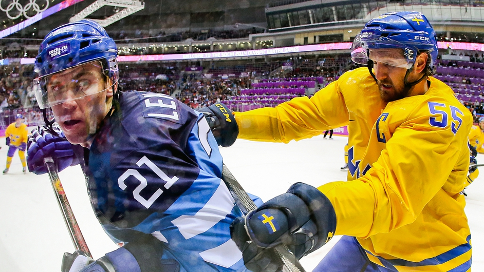 Jori Lehtera of Finland fights for the puck with Niklas Kronwall of Sweden during an ice hockey game at the Olympics in Sochi
