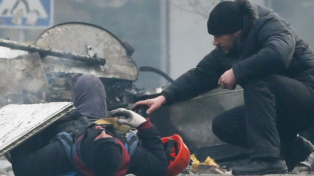A man tends to a wounded protester (Pic: EPA)