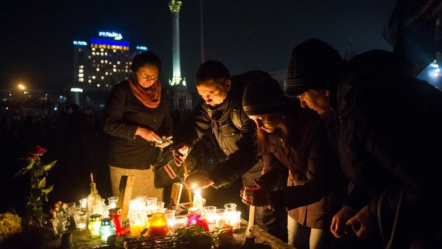 People light candles as they mourn opposition protesters were killed during clashes with police in the centre of Kiev