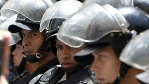 Members of the National Police stand guard as people protest against the government of Venezuelan President Nicolas Maduro during a demonstration in Caracas