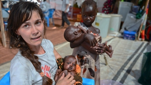 A Medecins Sans Frontieres (MSF) worker holds a South Sudanese baby as a vast vaccination campaign begins against cholera in the South Sudanese refugee camps