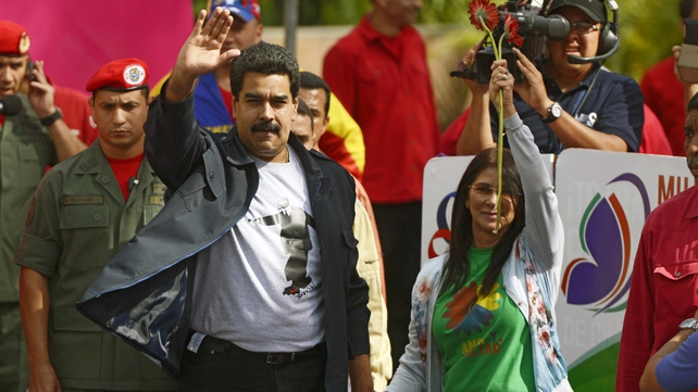 Venezuelan President Nicolas Maduro waves next to his wife Cilia Flores (R) as she holds flowers during a march in Caracas