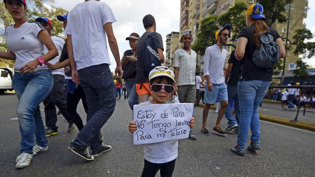 A girl holds a sign reading: 'I have no job. I don't have milk for my feeding bottle' during a protest against the government of Venezuelan President Nicolas Maduro in Caracas