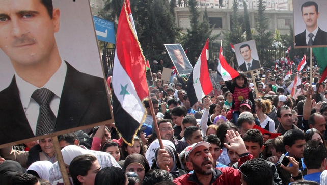 Syrians holding portraits of President Bashar al-Assad rally to show their support to the government yesterday in Damascus