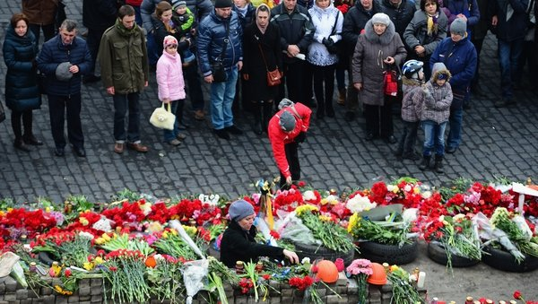 People view flowers left for anti-government demonstrators killed in clashes with police in Kiev