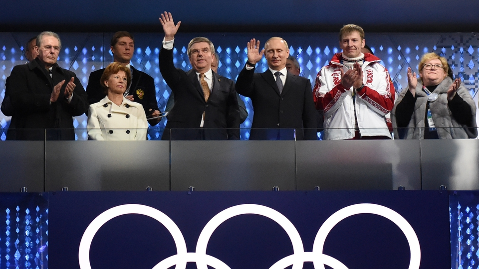 Former IOC president Jacques Rogge, current IOC president Thomas Bach (centre-left), Russia's President Vladimir Putin (centre-right) and double-gold medallist and bobsleigh pilot Alexander Zubkov (white jacket) watch on from the stands