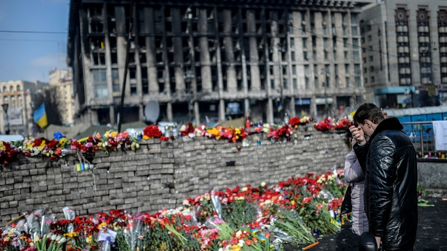 People leave flowers and mourn near a makeshift memorial in Kiev