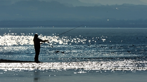 A man stands fishing at the shore of Lake Constance in brilliant sunshine in Langenargen, Germany (Pic: EPA)
